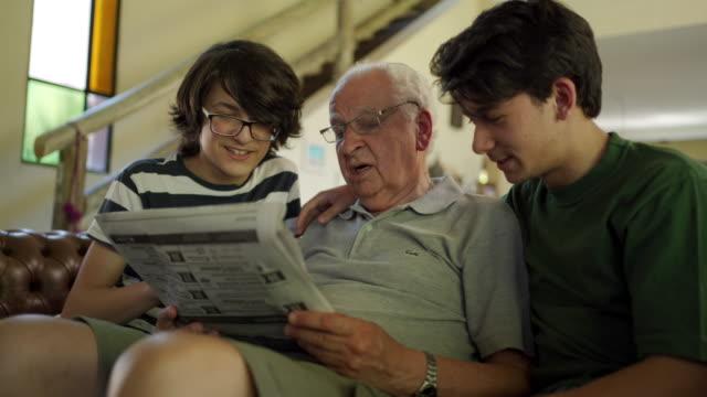 großvater liest zeitung mit enkeln - großeltern stock-videos und b-roll-filmmaterial