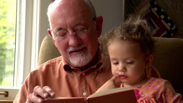 Grandfather reading to his granddaughter video