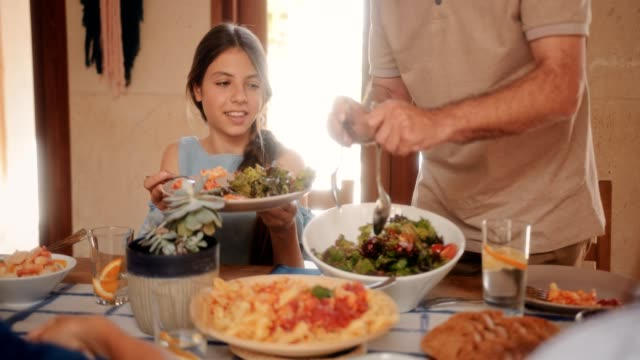 grandfather serving granddaughter fresh mediterranean salad at family lunch - italian food stock videos & royalty-free footage