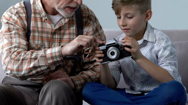 Grandfather showing boy vintage photo camera, creative family hobby, leisure