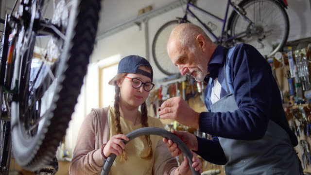 SLO MO Grandfather showing his granddaughter how to place a patch on the puncture of the bike's inner tube