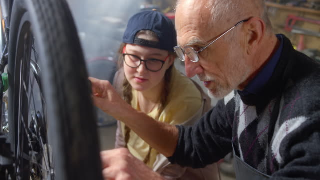 SLO MO Grandfather showing his teenage granddaughter how to oil the chain on her bicycle