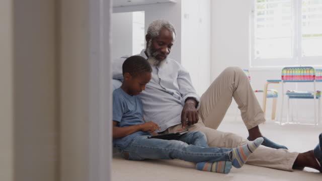 farfar sitter med barnbarn i childs sovrum använda digital tablet tillsammans - halvbild bildbanksvideor och videomaterial från bakom kulisserna