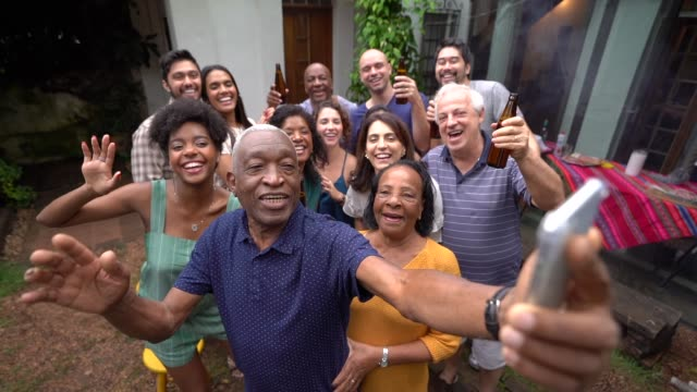 Grandfather taking a selfie of friends/family at barbecue party video