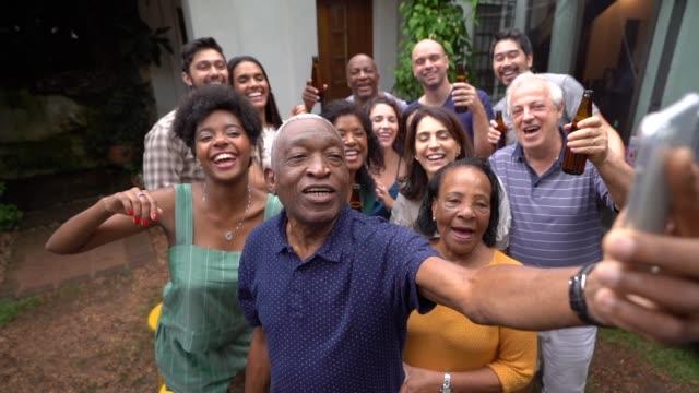 Abuelo teniendo un selfie de amigos y familiares en la fiesta de barbacoa - vídeo