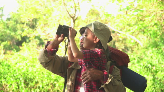 grandfather teach granddaugther use binoculars to see wild animals and bird inforest