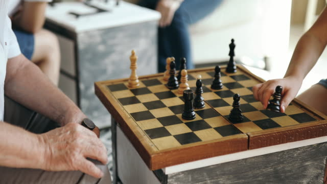 Grandfather teaches grandson how to play chess