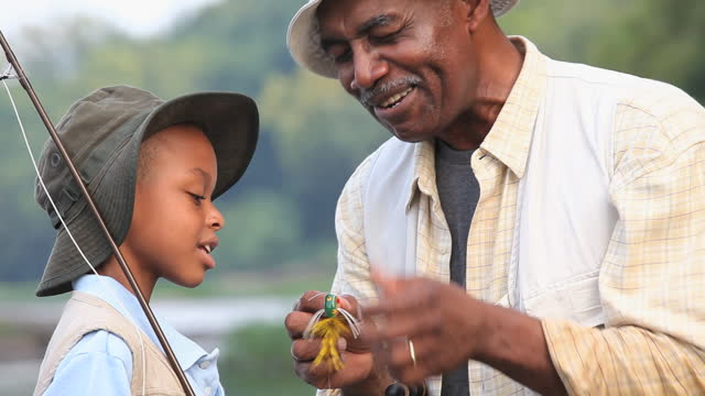 CU PAN  Grandfather teaching grandson (8-9) about fly fishing / Richmond, Virginia, USA  retirement stock videos & royalty-free footage