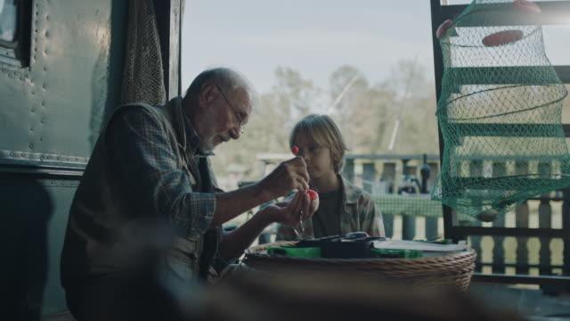 großvater lehrt enkel, wie man fischköder macht - angelhaken stock-videos und b-roll-filmmaterial