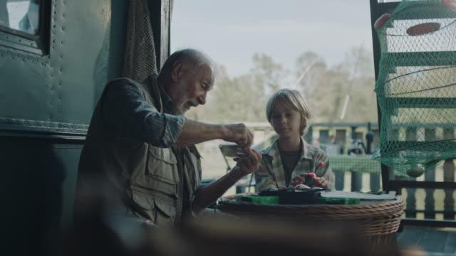 großvater lehrt enkel, wie man fischköder macht - fischköder stock-videos und b-roll-filmmaterial
