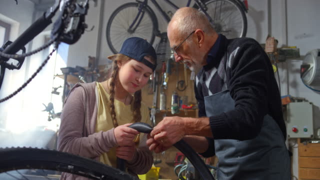 SLO MO Grandfather teaching his granddaughter how to mend a bike tire puncture in the workshop