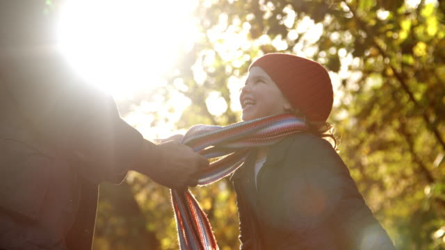 Grandfather Tying Granddaughter's Scarf On Autumn Walk video