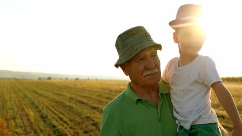 vídeos de stock e filmes b-roll de grandfather walking outdoors with grandson - cena rural