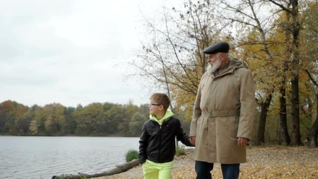 grandfather walks in autumn park near the river with little grandson - внук стоковые видео и кадры b-roll