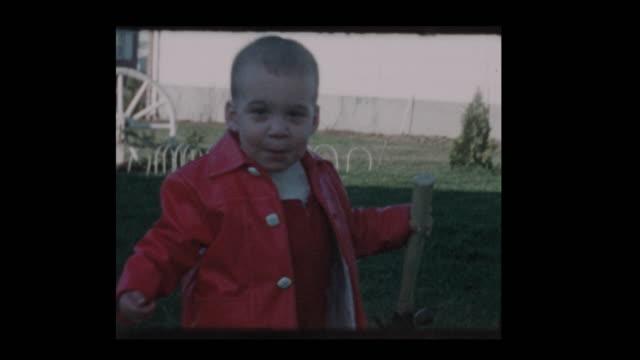 1961 祖父時計かわいい男の子をハンマーで果たしています。 - 金づち点の映像素材/bロール
