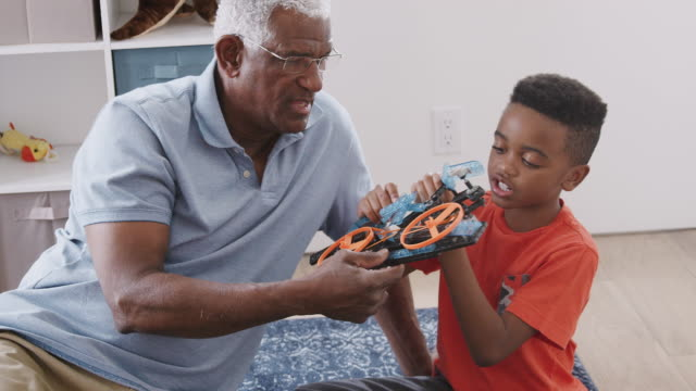 grandfather with grandson sitting on rug at home building model helicopter together - 8 9 anni video stock e b–roll