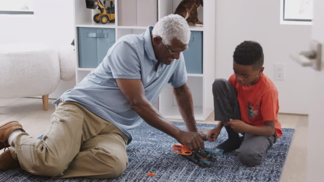 grandfather with grandson sitting on rug at home building model helicopter together - tappeto video stock e b–roll