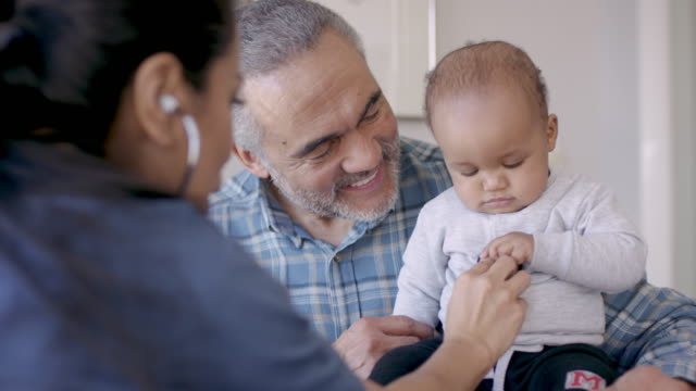 Grandfather With His Baby Grandson At Doctors Appointment An ethnic grandfather is holding his baby grandson while a hispanic female nurse uses a stethoscope to check the baby's vitals. general practitioner stock videos & royalty-free footage