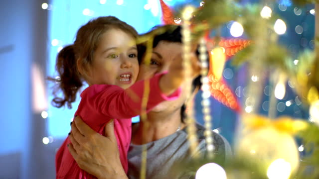 Grandma and granddaughter decorate the Christmas tree indoors video