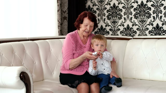 Grandma and grandson change channels with remote. video