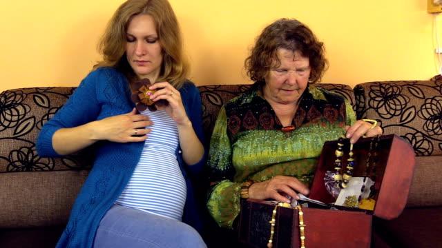 stockvideo's en b-roll-footage met grandma chose leather flower brooch gave pregnant granddaughter - halsketting
