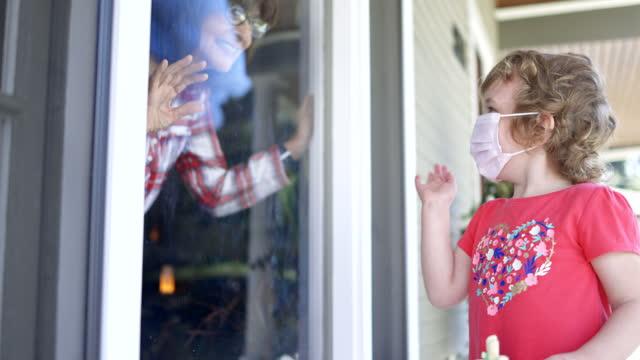 stockvideo's en b-roll-footage met de groet kleindochter van de oma door venster sociale distantiëring - raam bezoek