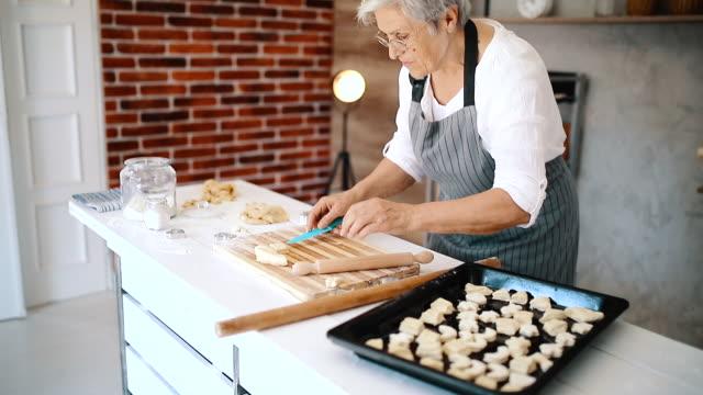 vídeos y material grabado en eventos de stock de la abuela hace bollos para sus nietos - galleta dulces