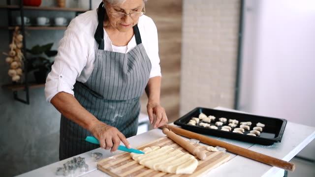 vídeos de stock e filmes b-roll de grandma makes buns for her grandchildren - baking bread at home