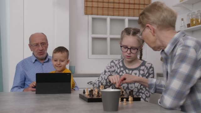 Grandma playing chess with granddaughter at home