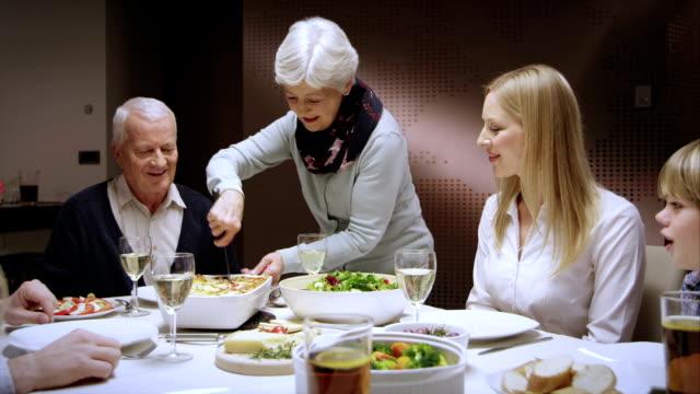 グランマを彼女の家族のラザニア - 家族での夕食点の映像素材/bロール