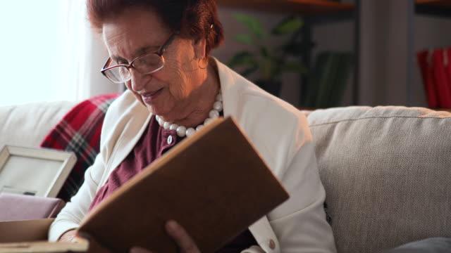 vídeos y material grabado en eventos de stock de abuela sentada en su casa y mirando fotos antiguas - árboles genealógicos