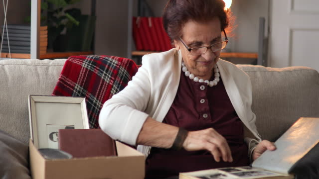 grandma sitting at home and looking at old photos - family trees stock videos and b-roll footage