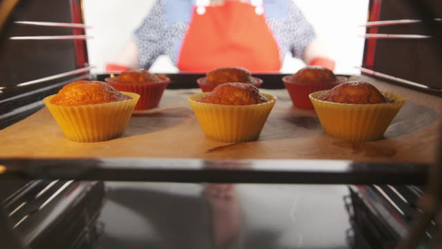 Grandma takes the fresh baked cupcakes out of the oven. Making homemade muffins video