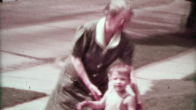 1937: Grandma walking suburban toddler boy as classic cars drive by. video