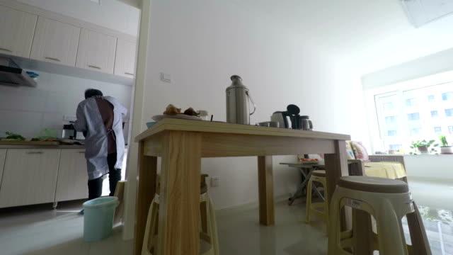 mormor som är upptagen matlagning - working from home bildbanksvideor och videomaterial från bakom kulisserna