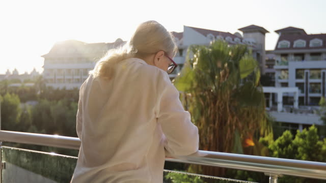 grandma with deep wrinkles stands on the balcony and waves her hand. - balcone video stock e b–roll