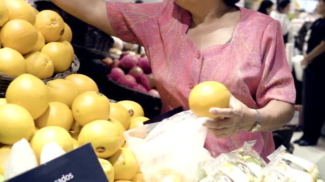 vidéos et rushes de grandmom choisit fruits et shopping au supermarché - marché établissement commercial