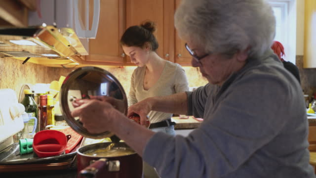 Grandmother adding ingredients to the pot she is using to cook with at the stove while her two granddaughter is also are cooking in the background.
