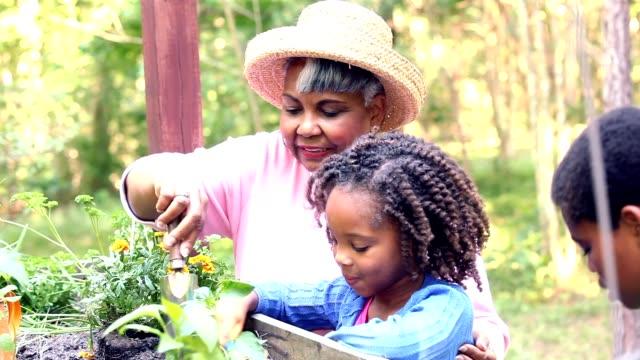 祖母と子供たちの春の屋外園芸します。 ビデオ