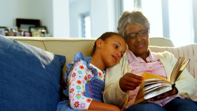 Grandmother and daughter reading book in living room 4k video