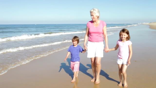 nonna e nipoti cammina lungo la spiaggia - nonna e nipote camminare video stock e b–roll