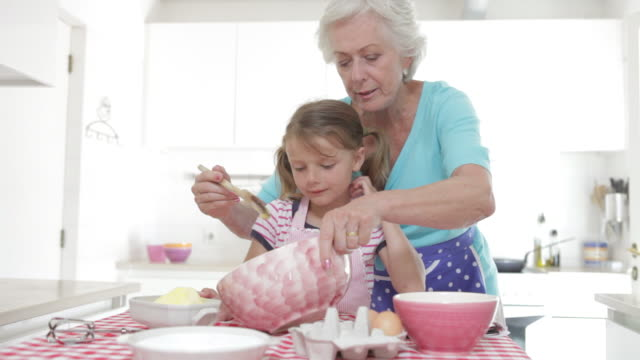Grandmother And Granddaughter Baking In Kitchen video