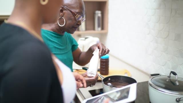 vídeos de stock, filmes e b-roll de avó e neta que cozinham o chocolate em casa - brigadeiro