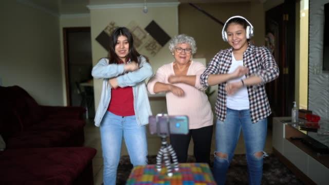 vidéos et rushes de grand-mère et petite-fille dansant et enregistrant utilisant le mobile à un vlog ou aux médias sociaux à la maison - culture des jeunes