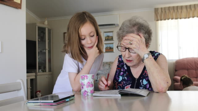 Grandmother and granddaughter doing crossword puzzle together