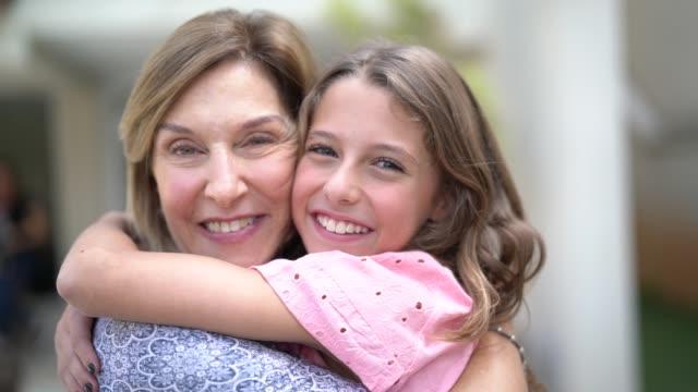 nonna e nipote che si abbracciano a casa - nonna video stock e b–roll