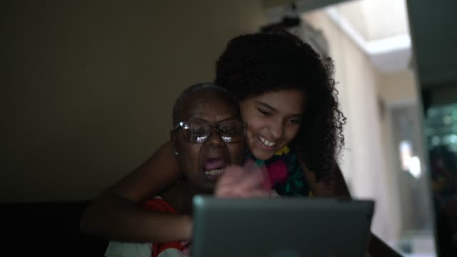nonna e nipote in videochiamata su tablet digitale a casa - nonna video stock e b–roll