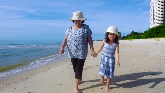 grandmother and granddaughter holding hands walking along beach - nonna e nipote camminare video stock e b–roll