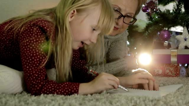 Grandmother and granddaughter lying on the floor near a Christmas tree. video