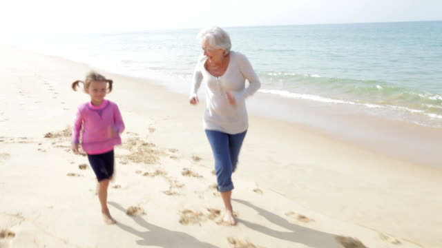Grandmother And Granddaughter Running Along Beach Together Grandmother and granddaughter run along the beach together. Shot on Canon 5d Mk2 with a frame rate of 30fps adult stock videos & royalty-free footage